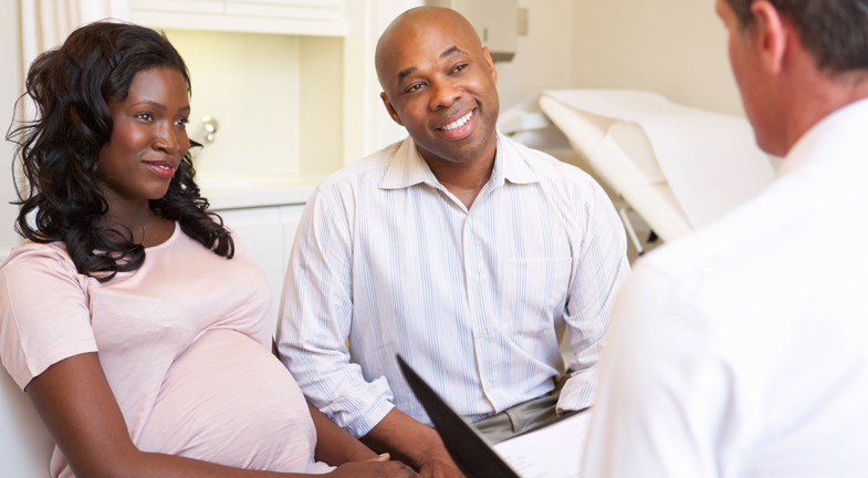 African American pregnant couple visiting with doctor